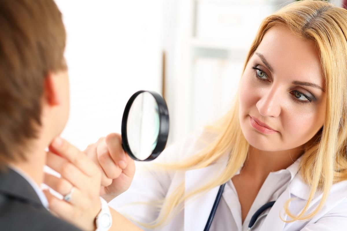 Woman Dermatologist Examining Patient's Face Skin with Magnifying Glass