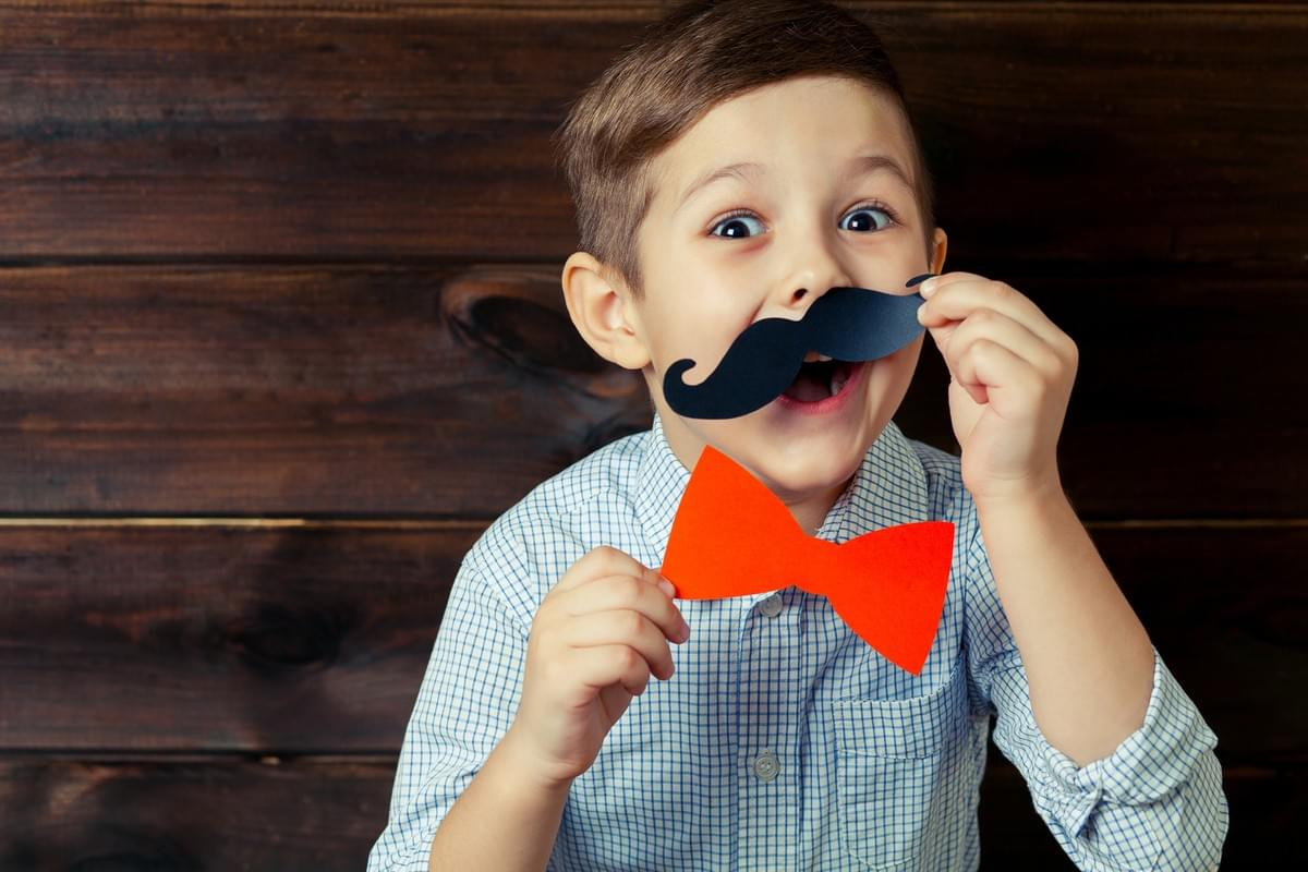 Funny Young Boy Playing around with Play Bow Tie and Mustache
