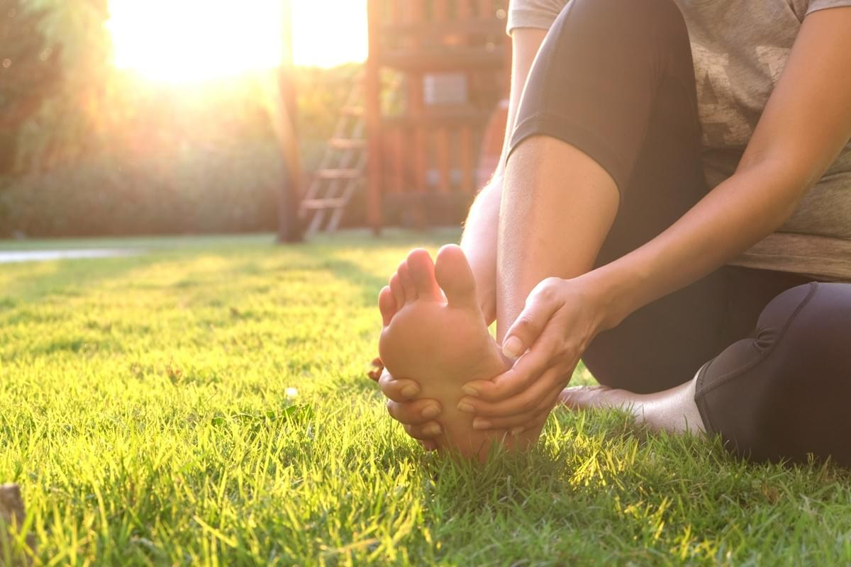 Woman sitting on grass holding painful foot