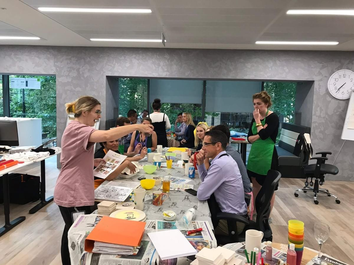 A group of Slalom employees say a table, being taught ceramic painting