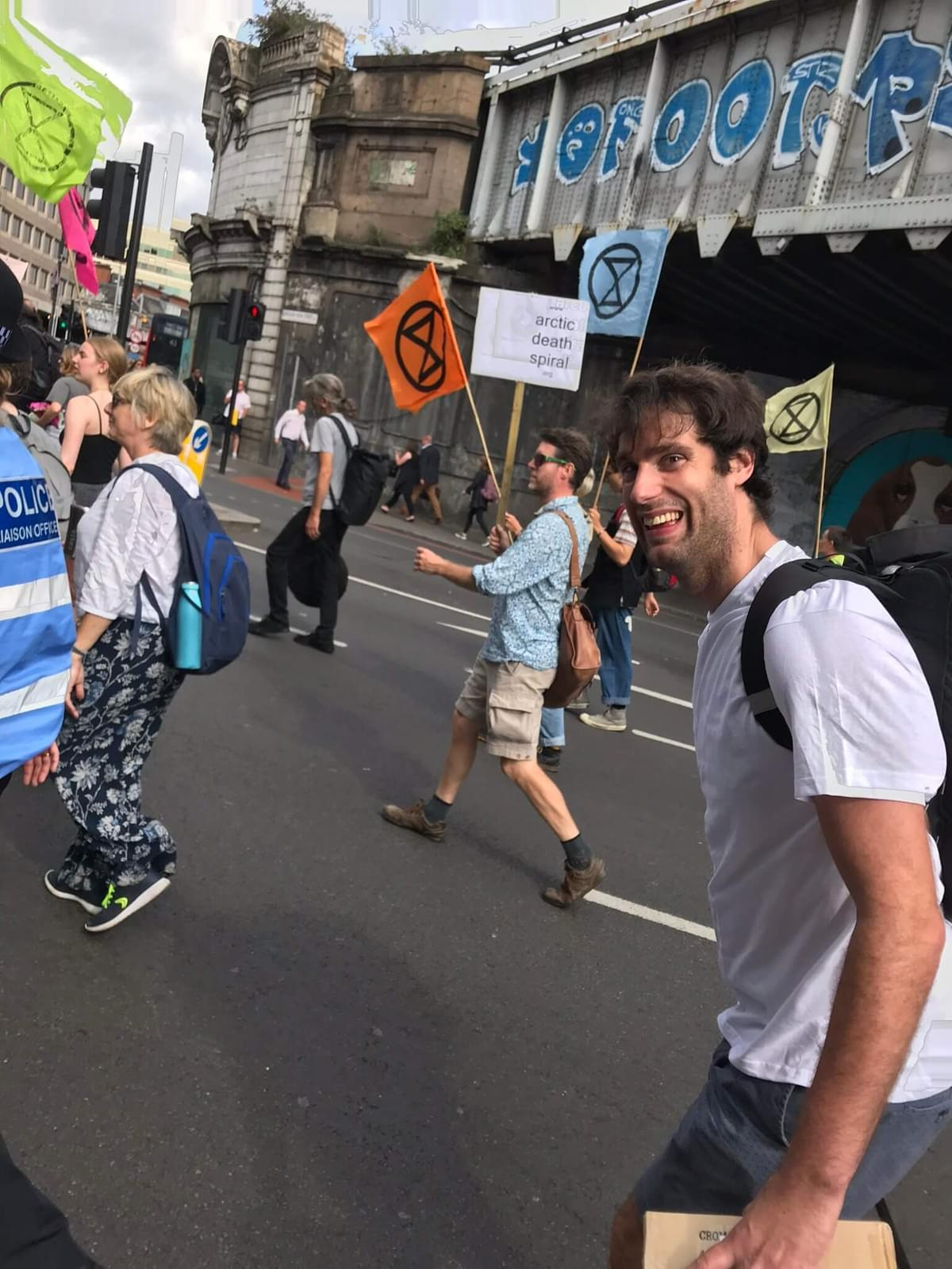 Sam walking down the street amongst Extinction Rebellion protesters