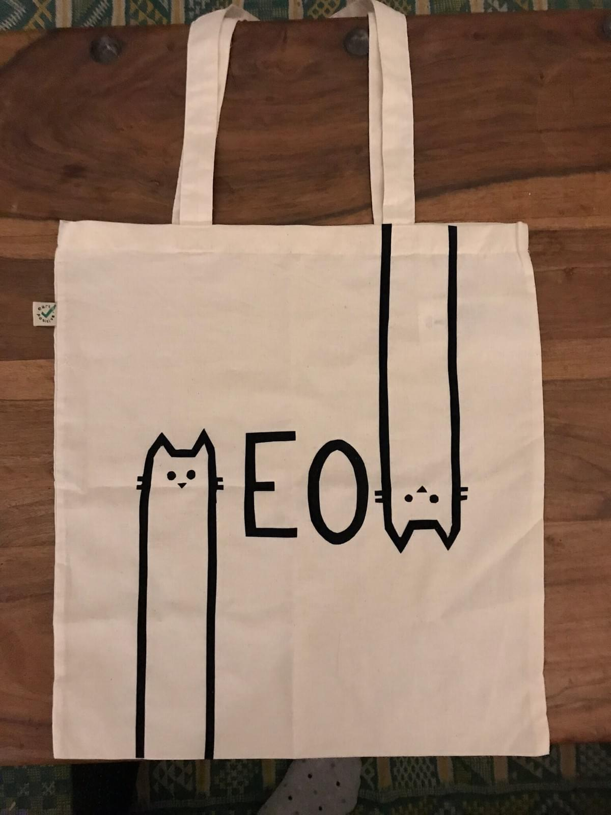 Printed tote bag with 'Meow' written across. The M and W are cat faces