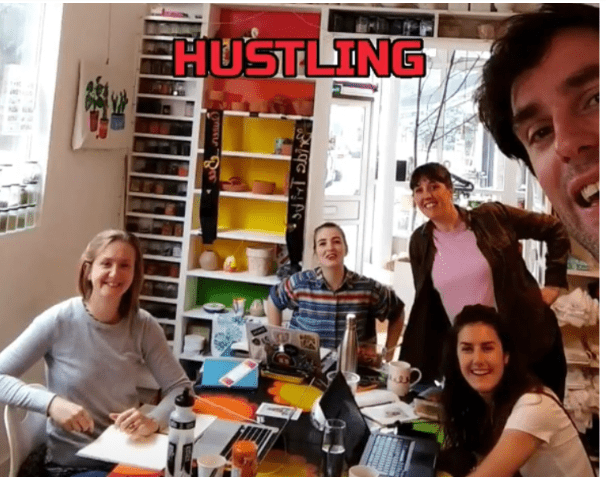 M.Y.O team on team hustle day sat around a table, smiling at the camera