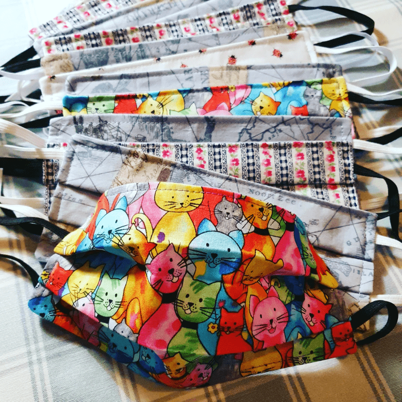 A pile of homemade fabric face coverings with elastic straps - the first in the pile is made of fabric with brightly coloured drawings of cats with smiling faces