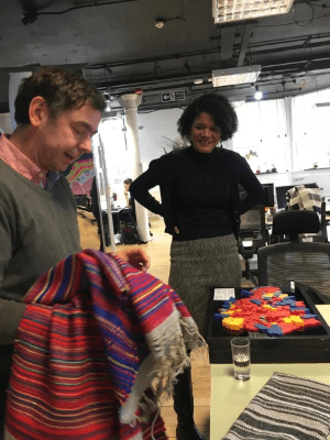 Julian from Open Data Manchester holding a striped woven cloth depicting election data. Julian is pointing to towards the data for Chi Onwurah's  constituency. Chi  stands smiling in the background.