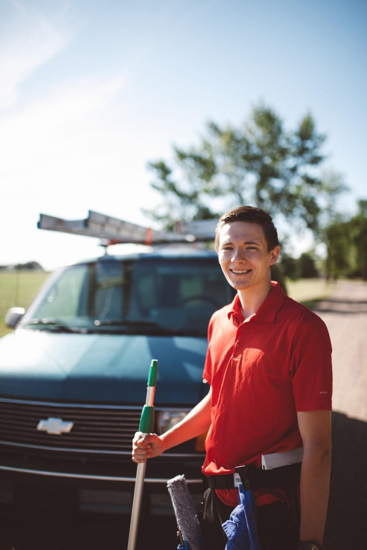 Ricky Feir with Window Cleaning Equipment, including a pole, scrubber, squeegee, and scraper in Moorhead by the Astro Van.