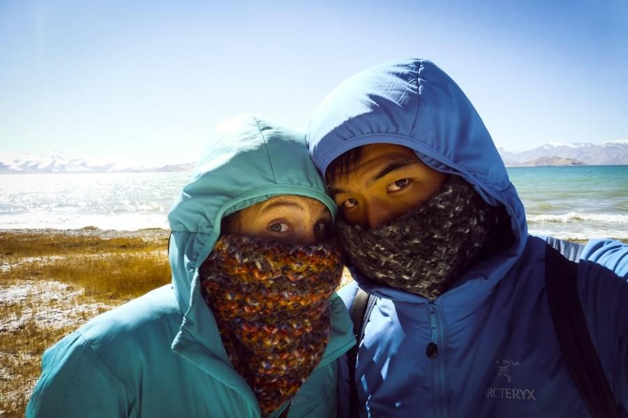 Image showing Kevin and Nicole freezing and wearing buffs at Karakul lake in Tajikistan.
