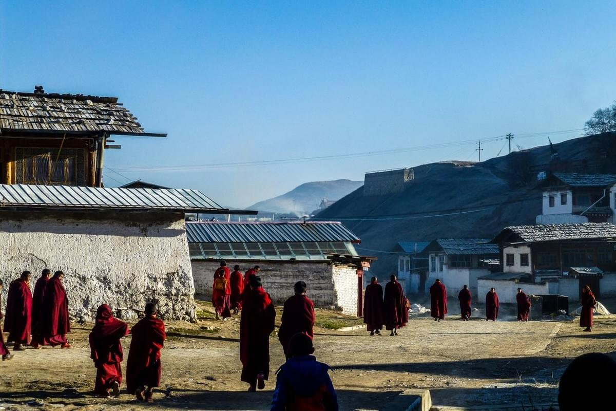 Image showing Tibetan monks in red robes walking around a monastery in Langmusi, China.