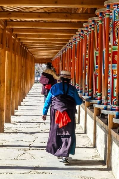 Image showing a Tibetan woman turning the prayer wheels at the Labrang monastery in Xiahe, China.