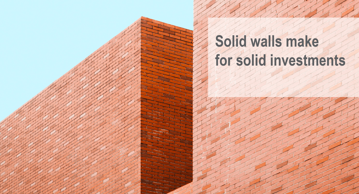 "This picture is of a brick wall which has ""Solid walls make for solid investments"" written on it."