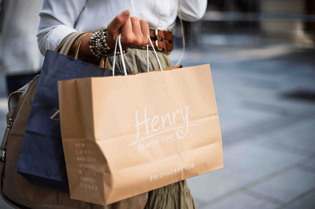 person holding brown shopping bag that says henry, holiday shopping, ad campaign, facebook ads