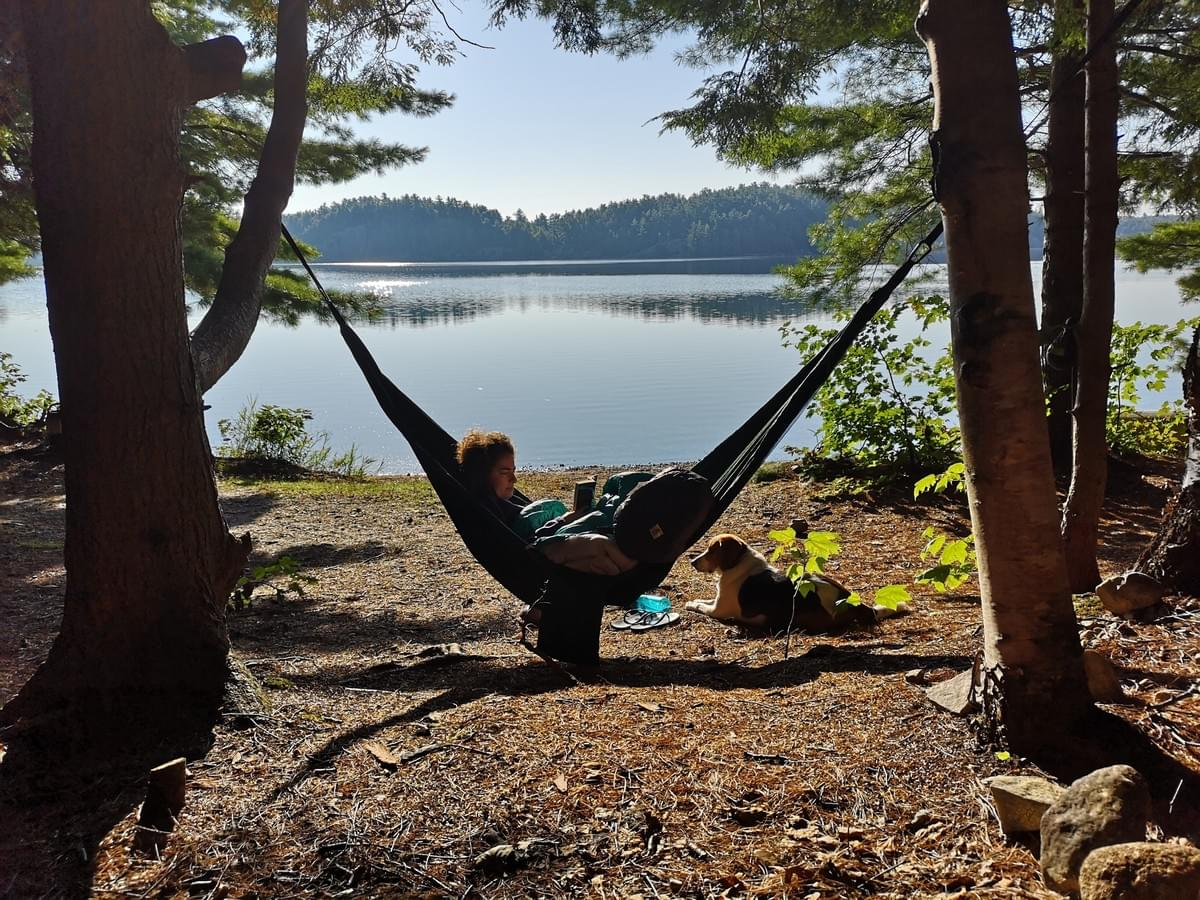 woman sits in a hammock and reads beside her dog at the edge of Killarney Lake