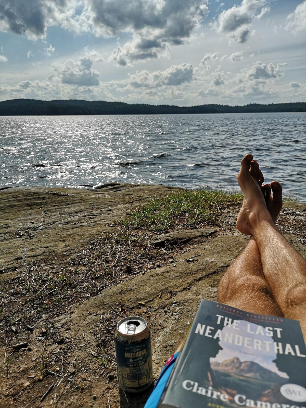 man laying down with a beer and a book beside Opeongo Lake, Algonquin Park