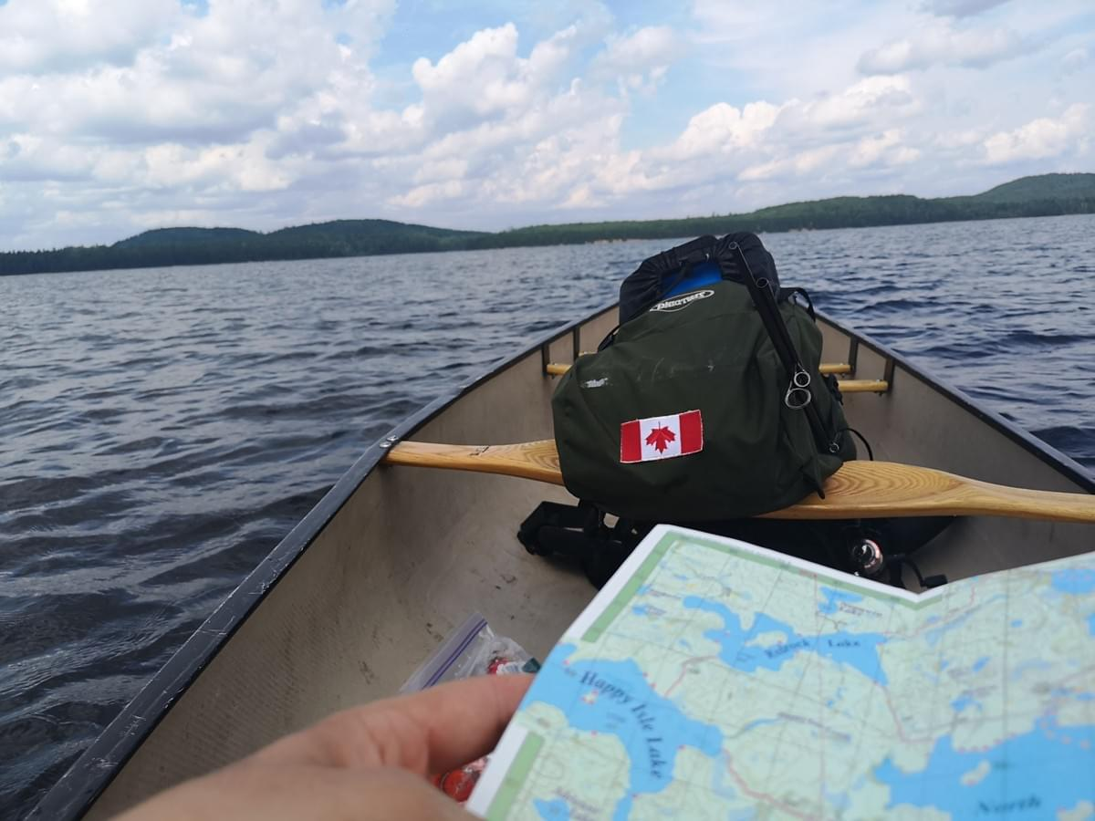 Man looking at a map in a canoe on Opeongo Lake, Algonquin Park