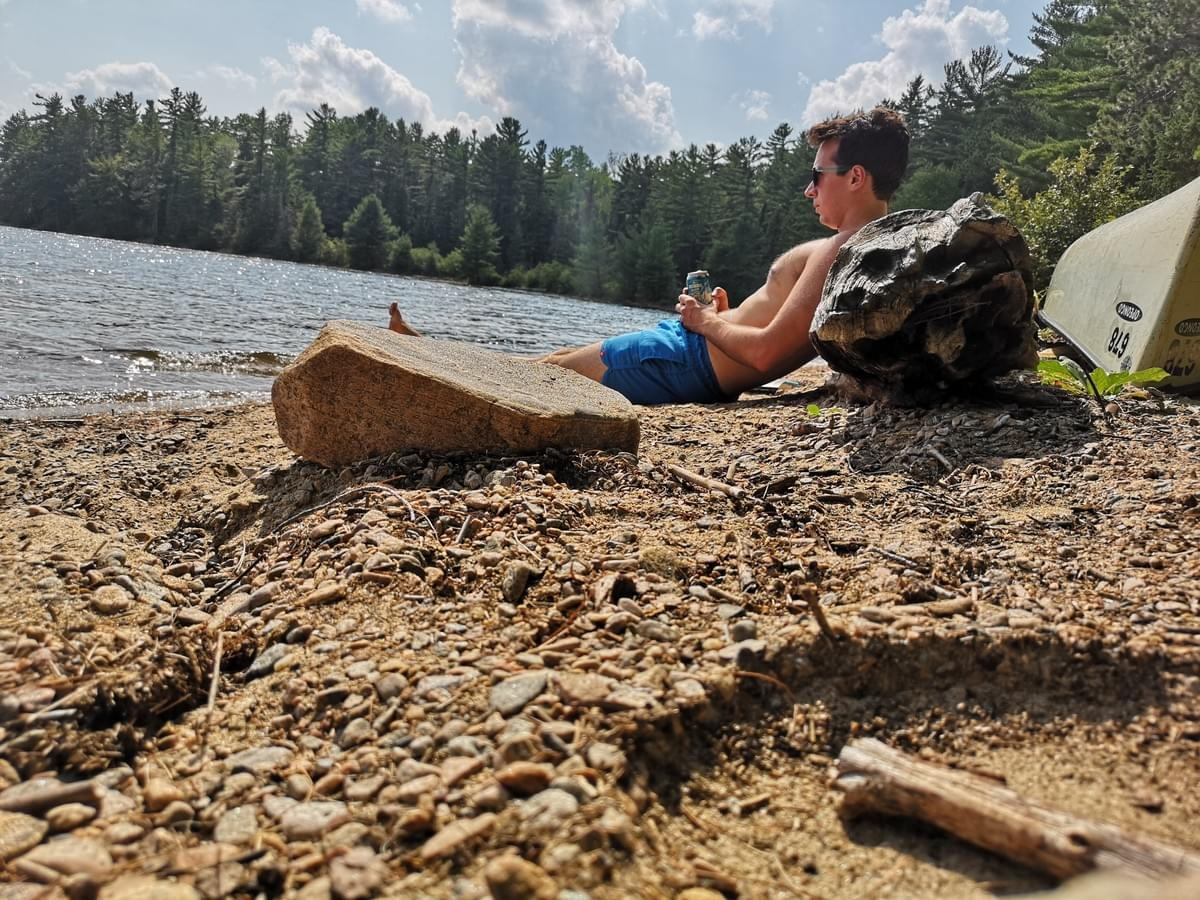 man laying against a log on a beach drinking a beer surrounded by trees and Opeongo Lake, Algonquin Park