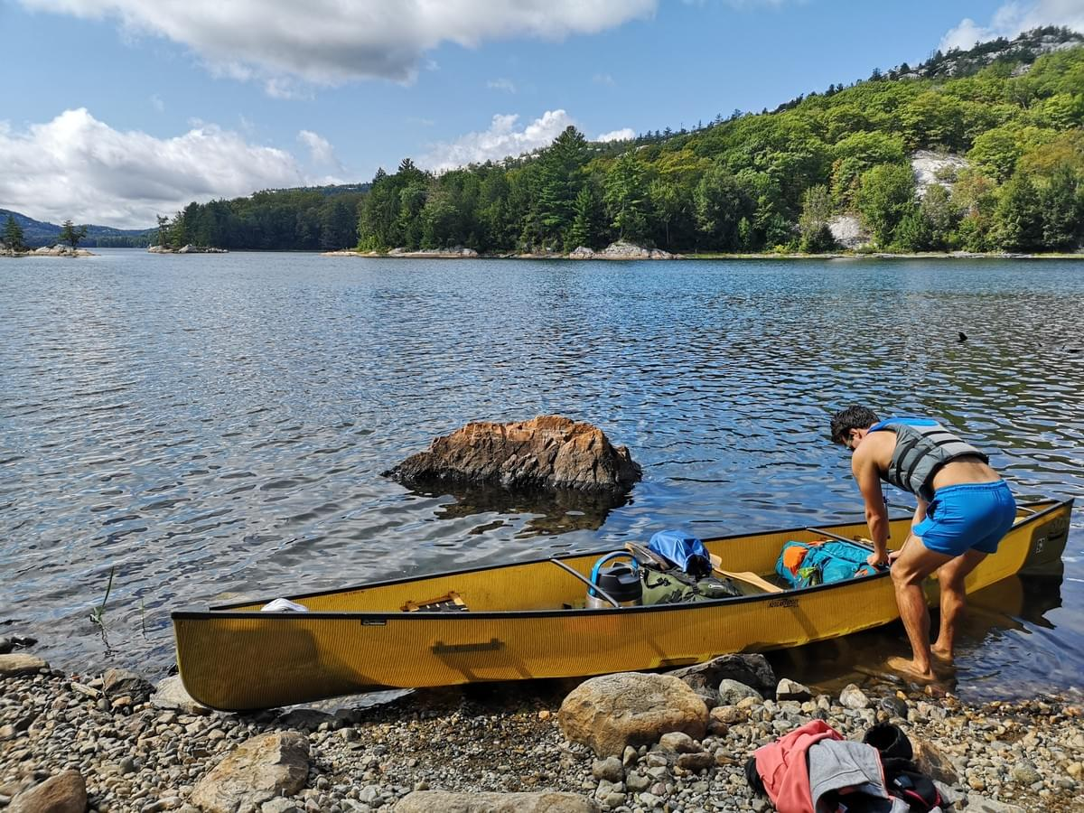 man loading a yellow canoe with camping gear at the edge of Killarney Lake Killarney Provincial Park
