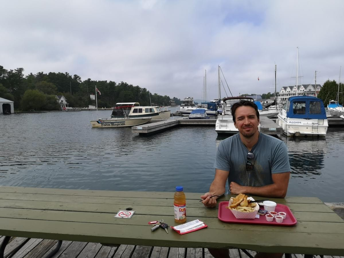 man sitting at a picnic table on a dock eating fish and chips at Herbert fish and chips in Killarney
