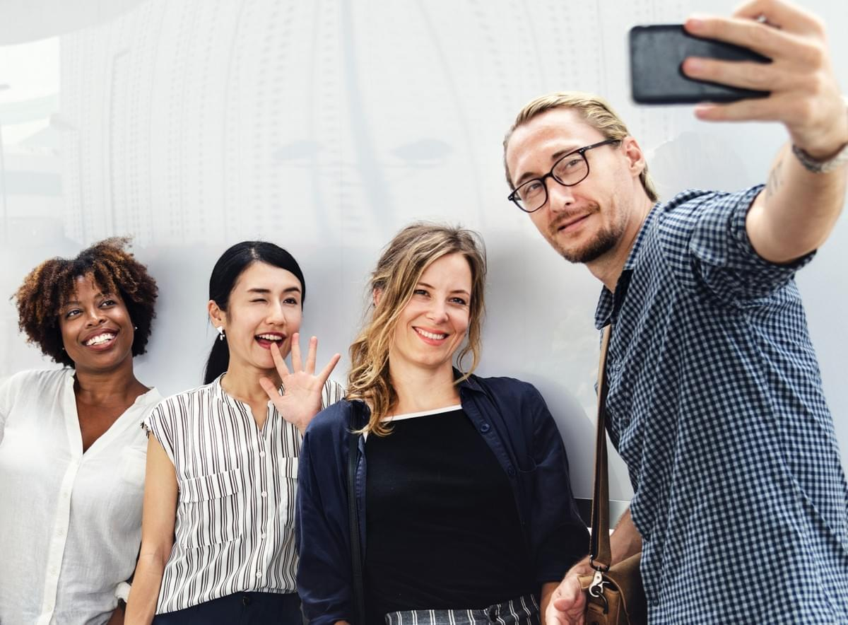 guy taking a selfie with three female coworkers to create interesting and entertaining content for Instagram
