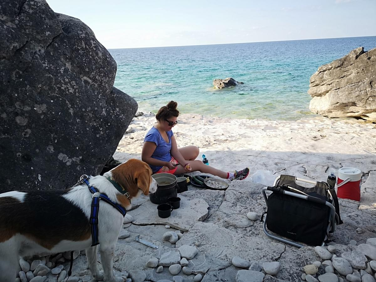 woman and her dog sitting beside the blue waters of Georgian Bay cooking dinner over a camping stove