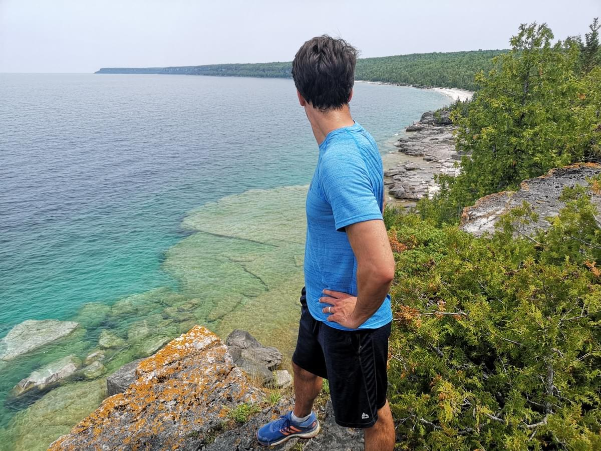 man standing on a cliff overlooking Bruce Peninsula, Georgian Bay, Ontario
