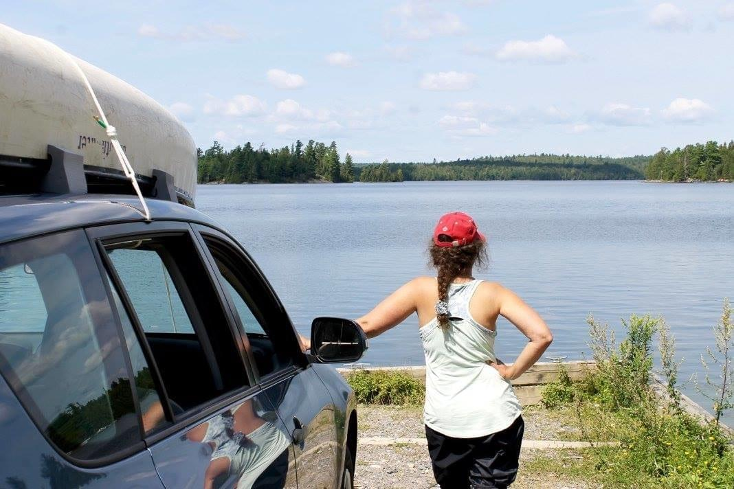 woman leans against a car with a canoe strapped to the top as she looks out onto Temagami lake
