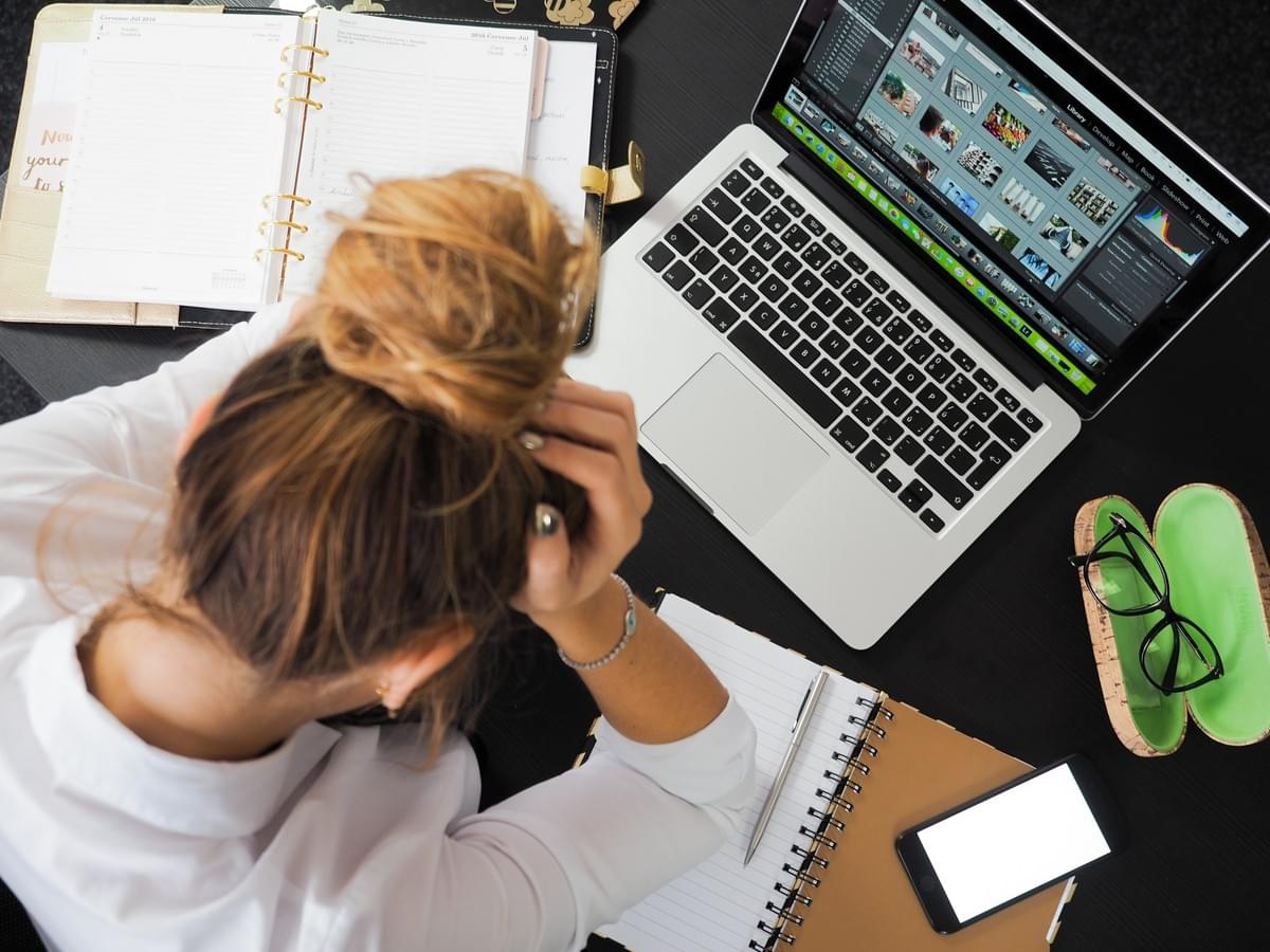 woman sitting at her work desk in front of laptop and books with her head in her hands visibly stressed