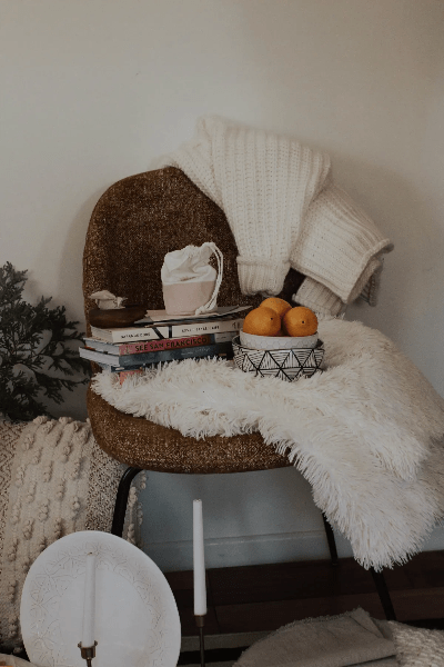mustard chair with books piled on top, with props, white candles, lemons in bowl, fur rug  by lilygrace lifestyle stock images