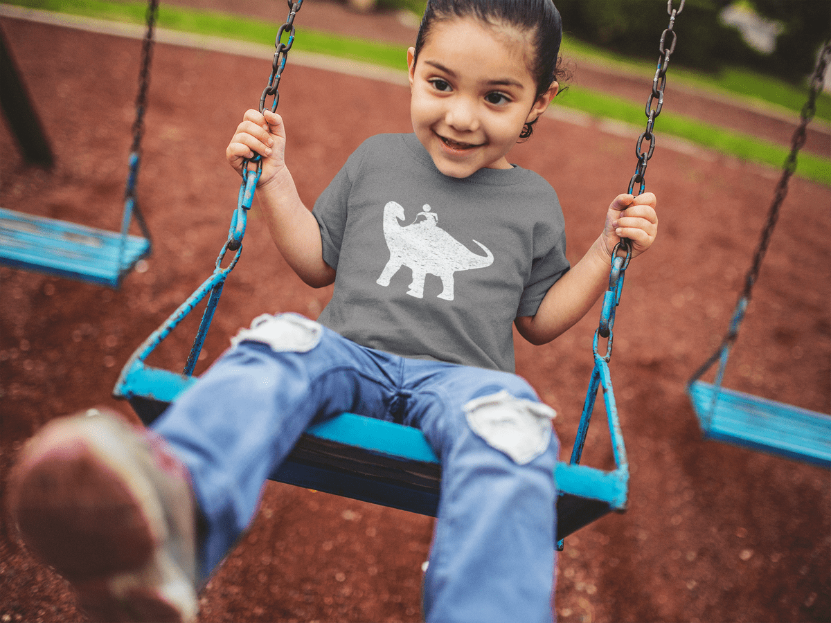 Kid swinging with a dinosaur riding t-shirt on.  Click to go to Amazon.com