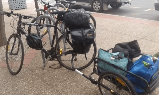 A bike with a trailer and pannier bags loaded with groceries