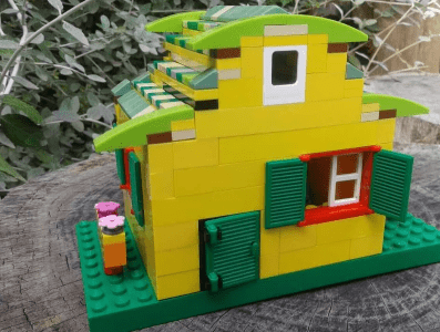 Lego sculpture of a green and yellow house