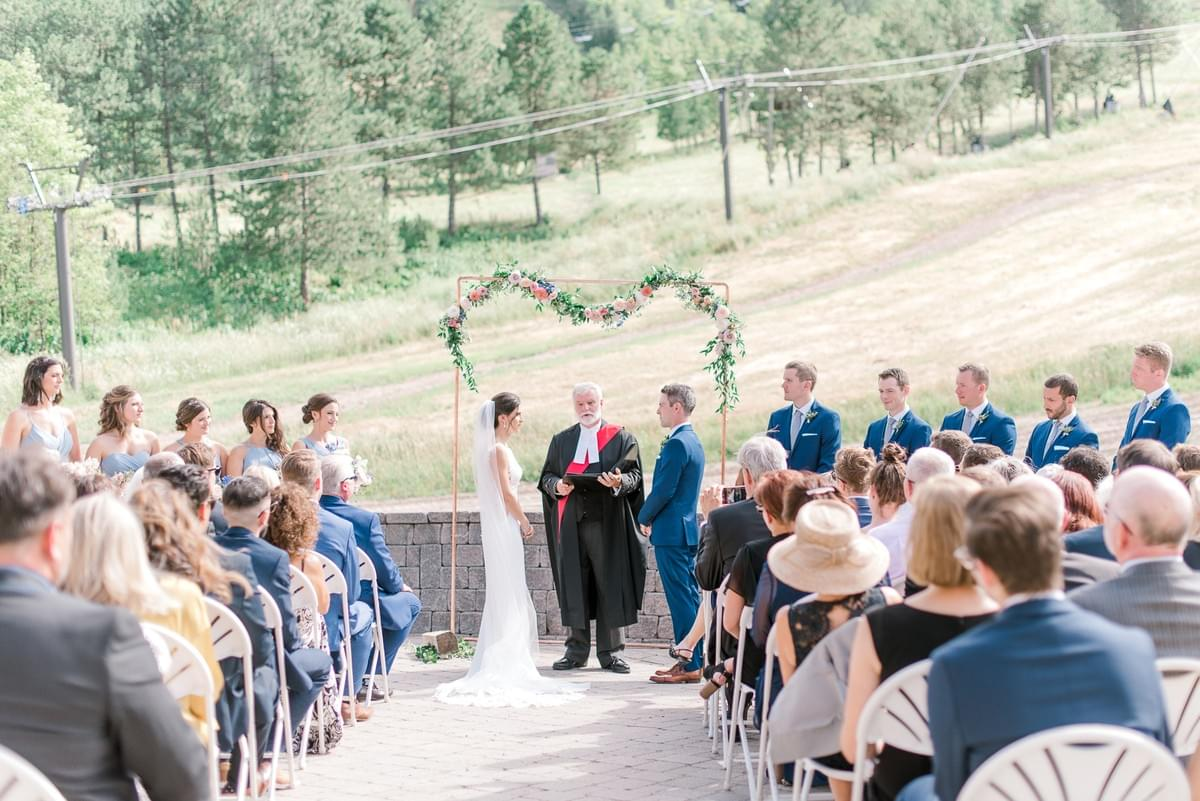 Floral garland on copper arch for airy, summer wedding ceremony at Craigleith Ski Club