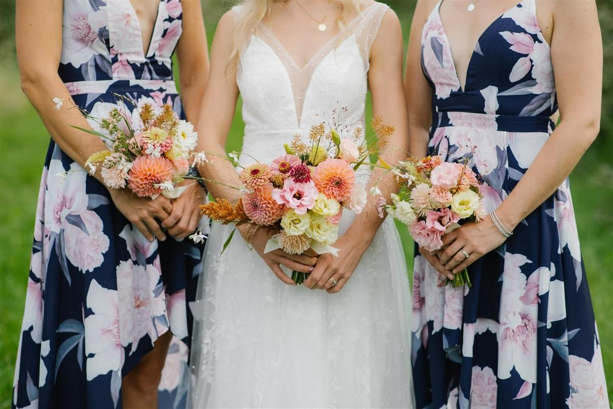 Peach and pink bridal and bridesmaid bouquets featuring local flowers at a barn wedding in Meaford, Ontario.