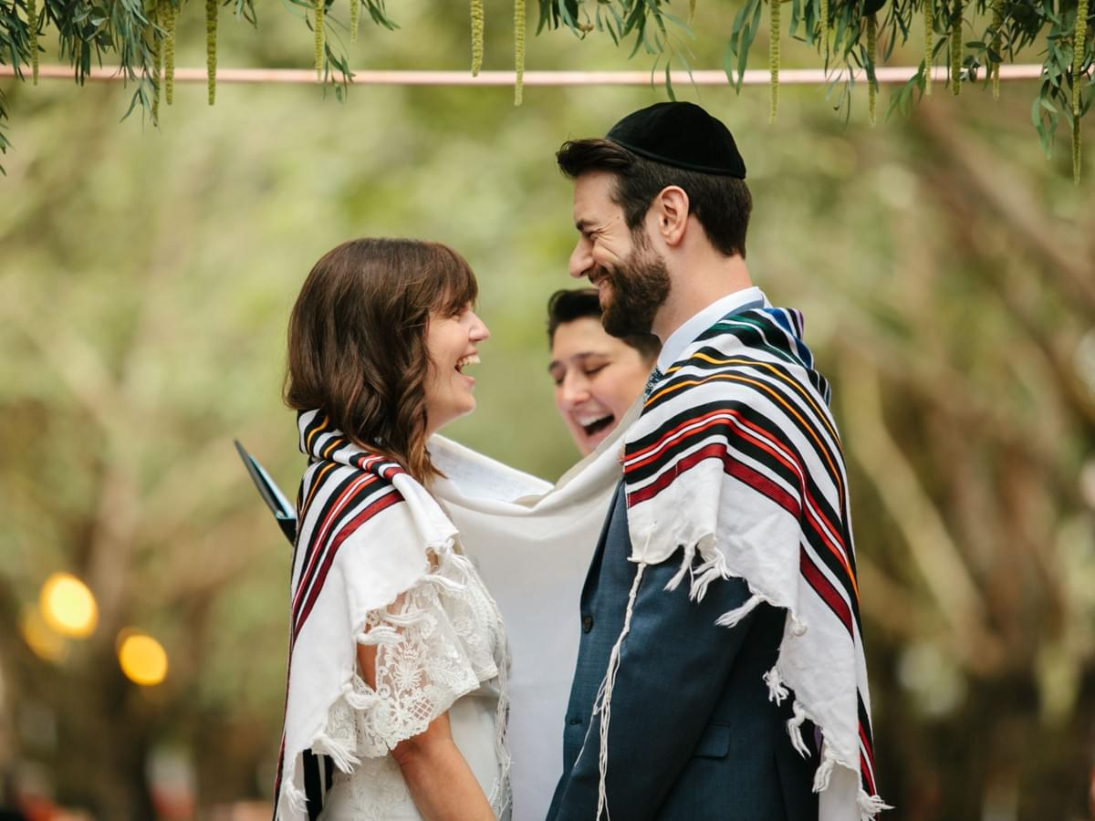 Couple draped in a tallit shares a laugh while the rabbi speaks during their wedding ceremony.