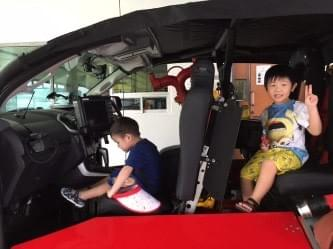 boys sitting in the red rhino at scdf fire station open house