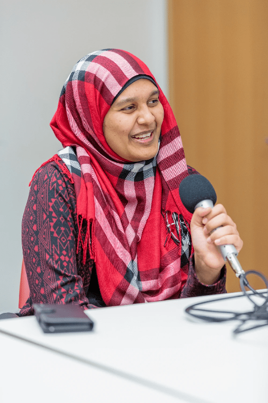 Farah speaking into a hand-held microphone.