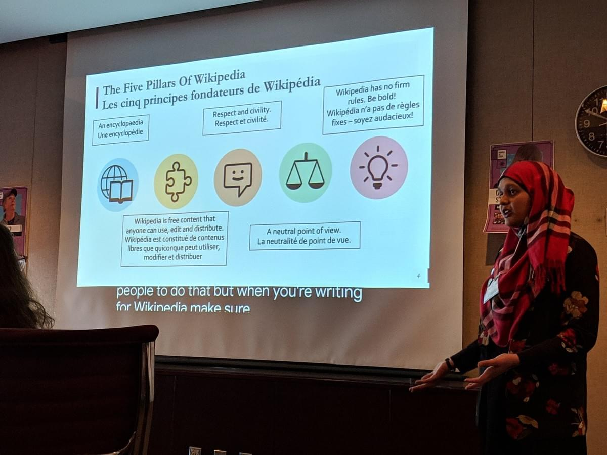 Farah speaks in front of a projected slide. Slide text: The Five Pillars of Wikipedia: an encyclopedia, free content that anyone can use, edit or distribute, respect and civility, neutral point of view, no firm rules - be bold!