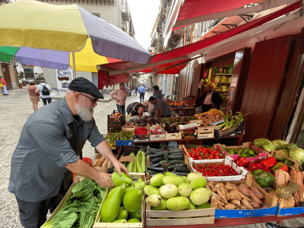Pete looking at produce in the market.