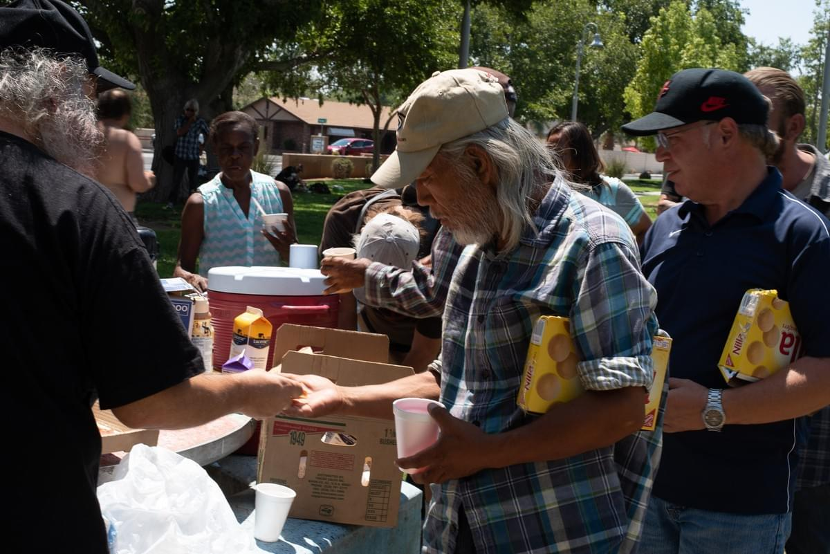 People gather around the table to receive their food provided by Food Not Bombs.  August 6, 2018, Las Vegas, NV.  Photo by Johnnie Wade