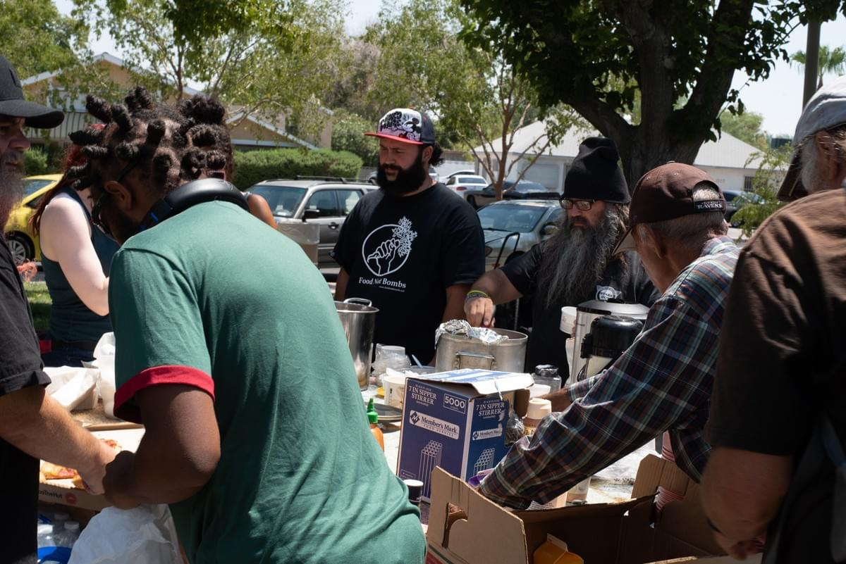 Food Not Bombs volunteers Joey Lankowski and Kelly Patterson (center) help serve food to those who have come to Circle Park.  August 6, 2018, Las Vegas, NV.  Photo by Johnnie Wade