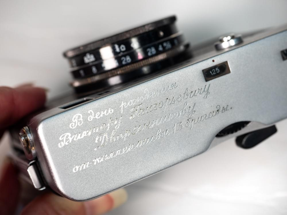 Photograph showing the engraving message on the top of the camera in Russian.