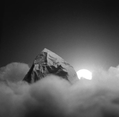 Paper mountain through soft toy filling clouds with a setting sun behind
