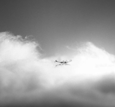 Miniature x-wing flying through soft toy filling clouds in black and white