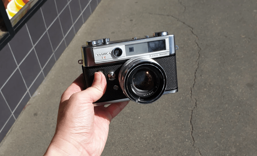 Yashica Ic Lynx 5000E camera held by a hand on a sunny day