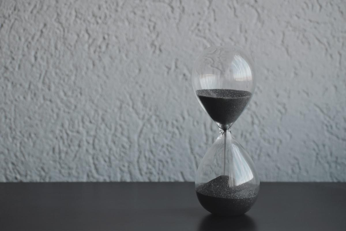 Image of an hourglass on a table representing the concept of time availability when considering a project manager