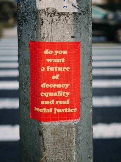"A pole at a street crossing with a red poster that says ""do you want a future of decency equality and real social justice"""
