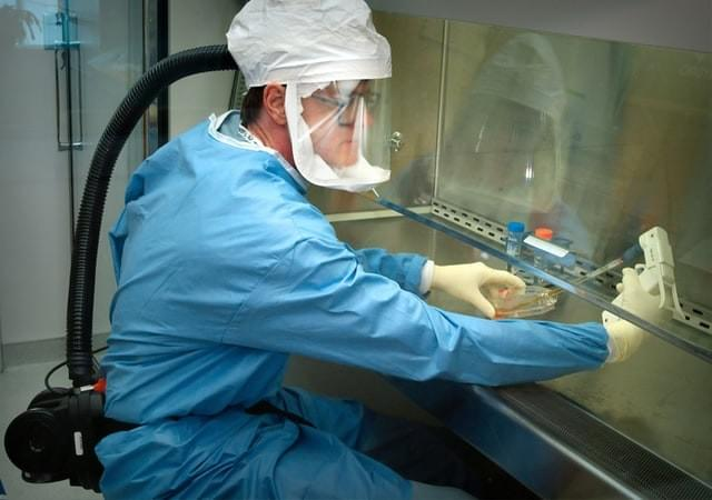 An image of a medical researcher in a blue suit with gloves, a hood, a ventilator, and clear face mask working with a pipette