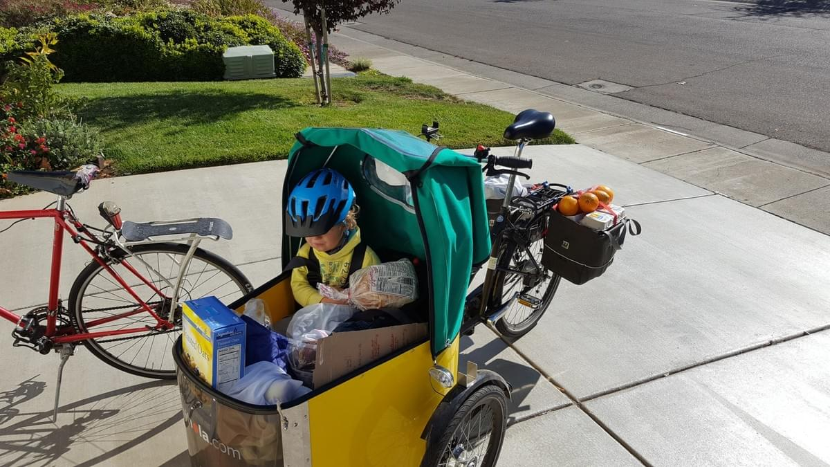 Nico and daughter pack up their Nihola Cargo Bike with groceries, ready to head home.