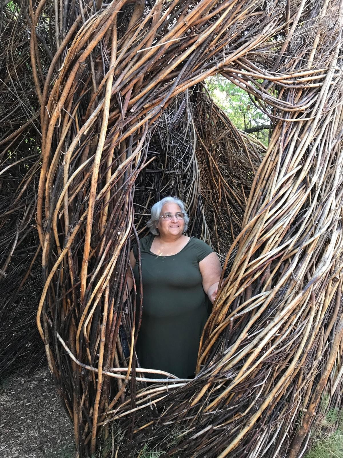 Image of Emily Levy looking through opening in sculpture made of branches