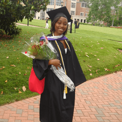 Picture of Krystle Kabare in her graduation robes smiling holding flowers
