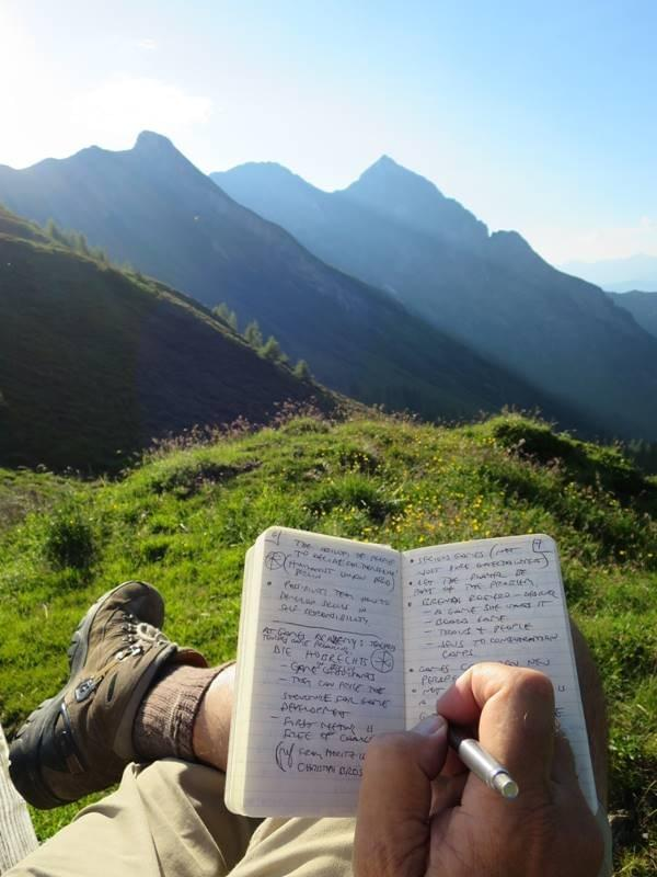 A person writing in their Beep! Book that's balanced on their legs, somewhere in nature with a very nice view of grassy hills and blue sky